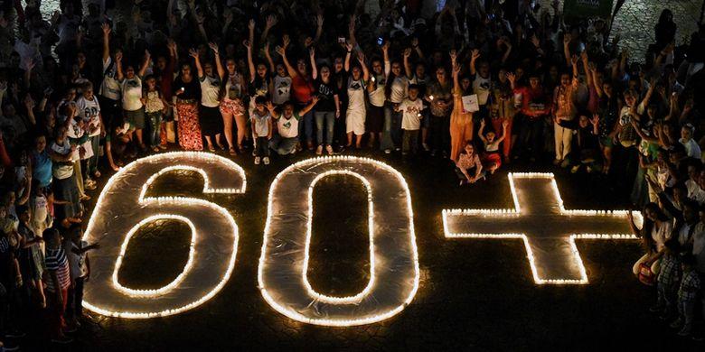 Masyarakat menyalakan lilin dan membentuk simbol 60+ dalam  kampanye lingkungan Earth Hour di Cali, Kolombia, Sabtu (24/3/2018). (AFP/Luis Robayo)