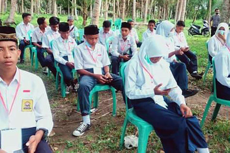 Puluhan siswa MTs Baiturrahman di Desa Salimuli, Kecamatan Galela Utara, Kabupaten Halmhera Utara, Maluku Utara, yang melaksanakan ujian madrasah (UM) di pinggir pantai, Sabtu (27/3/2021). Foto: Facebook (Jusnidar)