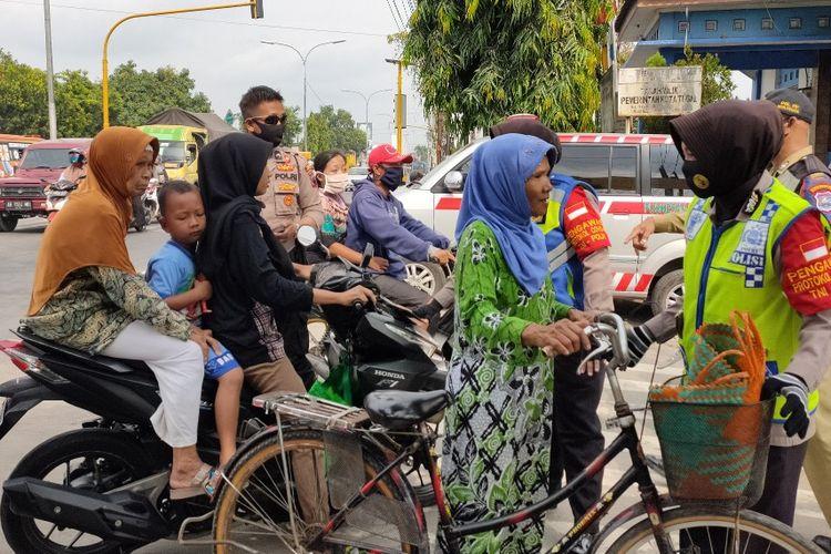 Petugas gabungan menghentikan warga tak memakai masker yang hendak masuk ke Pasar Sumurpanggang, Kota Tegal, Jawa Tengah, Rabu (10/6/2020)