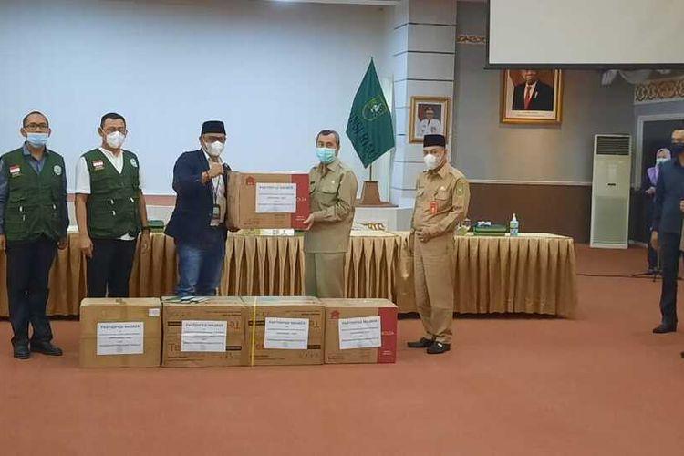Ketua Umum DPP Apkasindo, Gulat Medali Emas Manurung menyerahkan bantuan 50.000 masker kepada Gubernur Riau Syamsuar dalam mencegah wabah Covid-19, Senin (28/9/2020).
