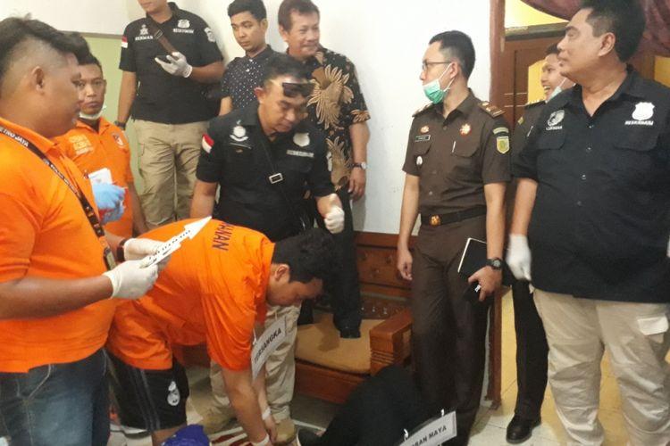 Haris Simamora tersangka pembunuhan satu keluarga di Bekasi saat memeragakan adegan rekonstruksi di rumah korban, Jalan Bojong Nangka II, Kecamatan Pondok Melati, Kota Bekasi, Rabu (21/11/2018).