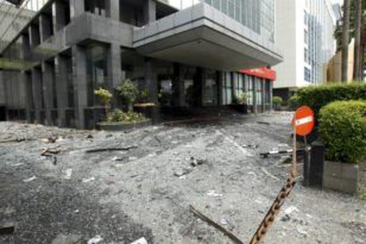 Petugas membersihkan pecahan puing kaca dan kertas yang berserakan di lokasi kebakaran di Wisma Kosgoro, Jalan MH Thamrin, Jakarta, Selasa (10/3/2015). Kebakaran yang terjadi pada Senin malam ini bermula dari lantai 16 dan merembet ke lantai 20. Penyebab kebakaran masih ditelusuri.