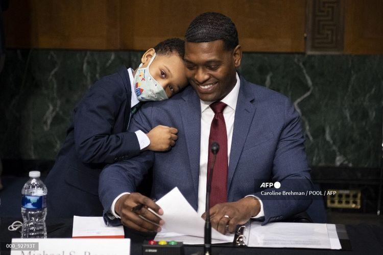 Calon Administrator Badan Perlindungan Lingkungan (EPA) Michael Stanley Regan dipeluk oleh putranya, Matthew, pada akhir sidang konfirmasi di hadapan komite Lingkungan dan Pekerjaan Umum Senat di Washington DC pada 3 Februari 2021.