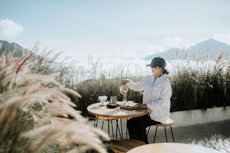 Pemandangan Gunung Batur di kejauhan bisa dinikmati sambil menyesap kopi di teras Montana del Cafe dikelilingi rerumputan yang cantik