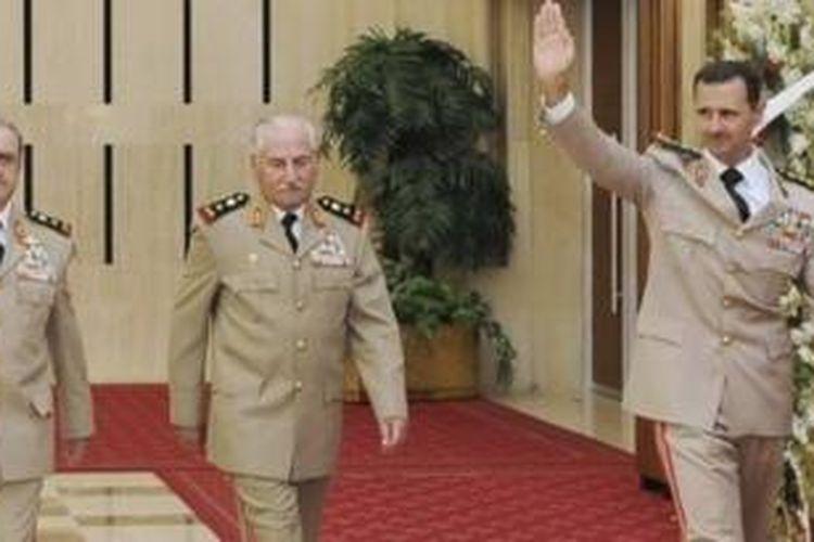 Presiden Suriah Bashar al-Assad bersama mantan Menteri Pertahanan Jenderal Ali Habib (tengah) dan Panglima Angkatan Bersenjata Jenderal Daoud Rajha pada Agustus 2010. Dikabarkan Ali Habib membelot dan kini berada di Turki.
