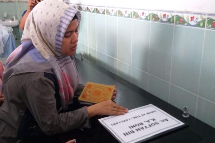 Fitriani (32) meratapi peti jenazah Sofyan (45) sopir taksi online yang menjadi korban perampokan, ketika berada di ruang kamar jenazah Rumah Sakit (RS) Bhayangkara Palembang, Sumatera Selatan, Jumat (16/11/2018). Sofyan sebelumnya ditemukan tewas dengan kondisi tinggal tulang.