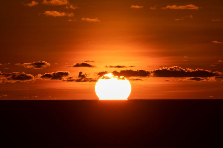 Matahari terbenam sempurna di atas lautan dilihat dari Bukit Paralayang Watugupit, Minggu (19/1/2020).