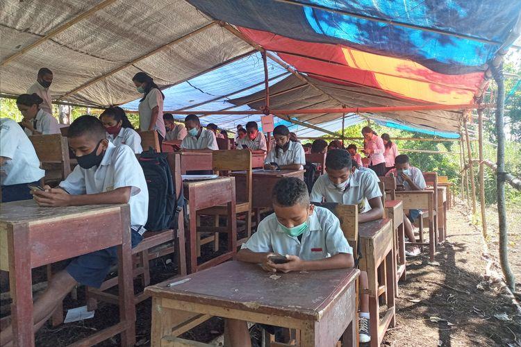 sebanyak 47 siswa dan siswi SMPN 04 Kota Komba melaksanakan Ujian Akhir Sekolah (UAS) berbasis digital dibawah tenda darurat di tengah hutan di Gunung Wokonggoro, Kampung Gurung, Desa Gunung, Kecamatan Kota Komba, Kabupaten Manggarai Timur, NTT, Senin, (12/4/2021). Ujian dilaksanakan dari Senin, (12/4/2021) sampai Kamis, (15/4/2021). (KOMPAS.com/MARKUS MAKUR)