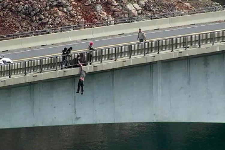 Seorang pria dipegang oleh anggota Sheriff Tuolomne County, California, Amerika Serikat, pada Senin (8/2/2021). Pria itu diselamatkan setelah hendak bunuh diri dengan melompat dari jembatan.