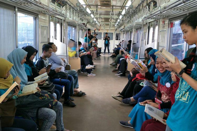 Relawan pegiat literasi mengampanyekan aksi membaca buku di dalam KRL dari Stasiun Jakarta Kota sampai Stasiun UI dalam rangka hari buku sedunia, Minggu (22/4/2018).