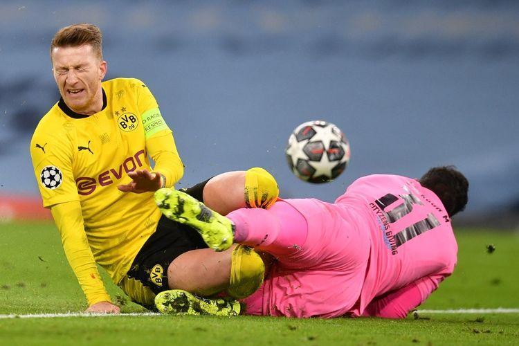 Manchester City menang tipis 2-1 atas Borussia Dortmund pada laga leg pertama babak perempat final Liga Champions, Rabu (7/4/2021) dini hari WIB. Kapten Dortmund Marco Reus dan kiper Man City Ederson berduel dalam foto ini.