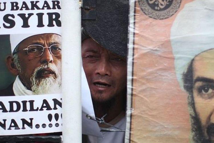 Seorang pendukung Abu Bakar Baasyir memegang spanduk bergambarkan Baasyir dan pemimpin Al Qaeda kala itu, Isama bin Laden, Pengadilan Negeri Jakarta Selatan pada 16 Juni 2011.