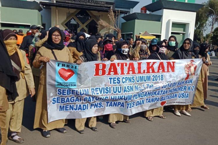 Ratusan honorer Kategori 2 di Karawang berunjuk rasa di depan Kantor Pemkab Karawang, Selasa (18/9/2018). Mereka menuntut Pemkab Karawang menolak seleksi CPNS 2018.