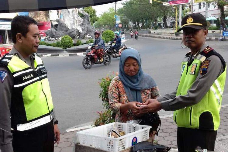 Widiyanti (33), seorang penjaja sayur keliling di Kebumen, Jawa Tengah saat menyerahkan segepok uang kepada Polisi, Kamis (29/6/2017).