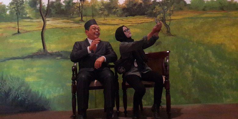 Seorang wisatawan saat berfoto selfi bersama patung Presiden ke-4 RI Abdurrachman Wahid atau Gus Dur di The Legend Star, Jatim Park 3, Kota Batu, Jawa Timur, Jumat (29/12/2017).