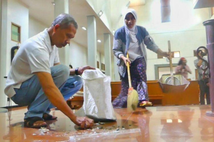Jirhas Rani (kanan) saat membantu membersihkan Gereja Santa Lidwina di Bedog, Sleman, Yogyakarta, Senin (12/2/2018), dengan seorang warga. Jirhas datang bersama suaminya, Ahmad Muttaqin (tidak tampak dalam gambar).