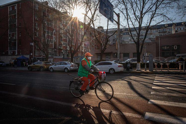 Seorang pekerja kota mengenakan masker pelindung wajah mengendarai sepeda di Beijing, China, 22 Februari 2020.  EPA-EFE/ROMAN PILIPEY
