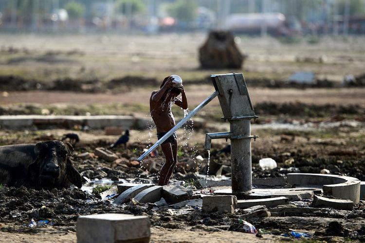 Bocah India di Allahabad menyiramkan air ke tubuhnya untuk melawan cuaca panas yang dapat mencapai lebih dari 50 derajat celcius.
