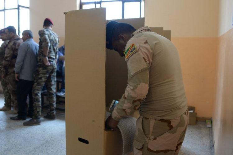 Seorang anggota pasukan keamanan Irak memberikan suaranya pada pemungutan suara awal untuk pemilihan parlemen, di Mosul, irak, Kamis (10/5/2018). (AFP/Zaid Al-Obeidi)