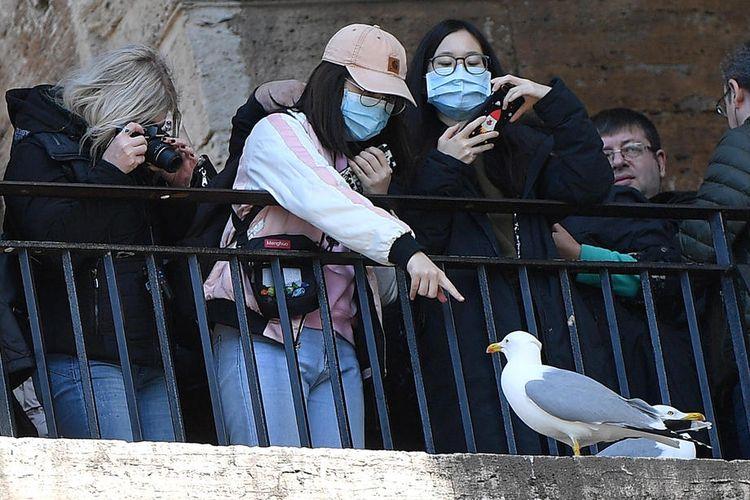 Turis yang memakai masker pelindung mengunjungi Roma, Italia, 26 Februari 2020. Menurut statistik resmi terbaru, lebih dari 370 orang telah terinfeksi oleh virus corona Wuhan, dan setidaknya 12 orang meninggal karena COVID-19 di negara Mediterania sejauh ini. EPA-EFE/ETTORE FERRARI