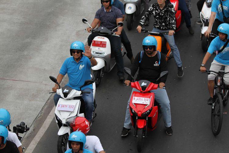 Gubernur DKI Jakarta Anies Baswedan melambaikan tangan saat konvoi menggunakan kendaraan elektrik di Festival Langit Biru, Bundaran Senayan, Jakarta Pusat, Minggu (27/10/2019). Kampanye tersebut bertujuan mengenalkan kendaraan listrik yang ramah lingkungan guna mengurangi polusi udara.