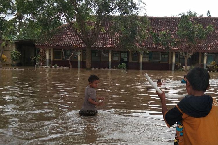 Anak-anak penyintas banjir Desa Kalangligar tengah bermain air di halaman SD Karangligar 1 yang terendam banjir, Rabu (26/2/202).