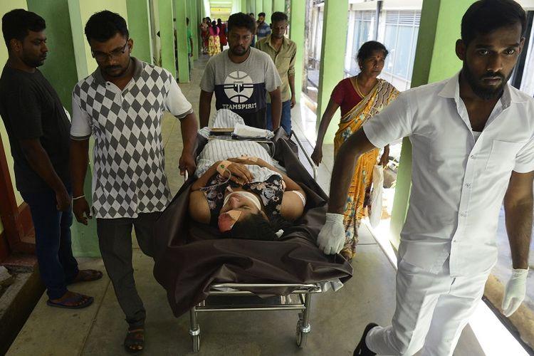 Seorang perempuan yang terluka dibawa dengan tandu di sebuah rumah sakit usai ledakan bom di sebuah gereja di kota Batticaloa, Sri Lanka, Minggu (21/4/2019).