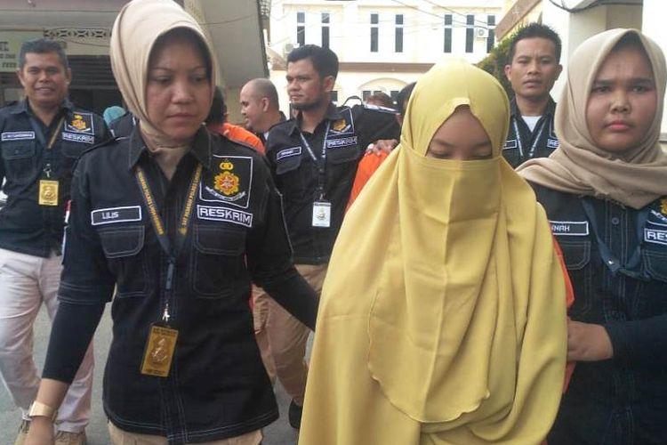 Polisi membawa NA (21) salah satu tersangka dalam kasus penyebaran berita bohong di Mapolres Lhokseumawe, Aceh, Rabu (17/7/2019)
