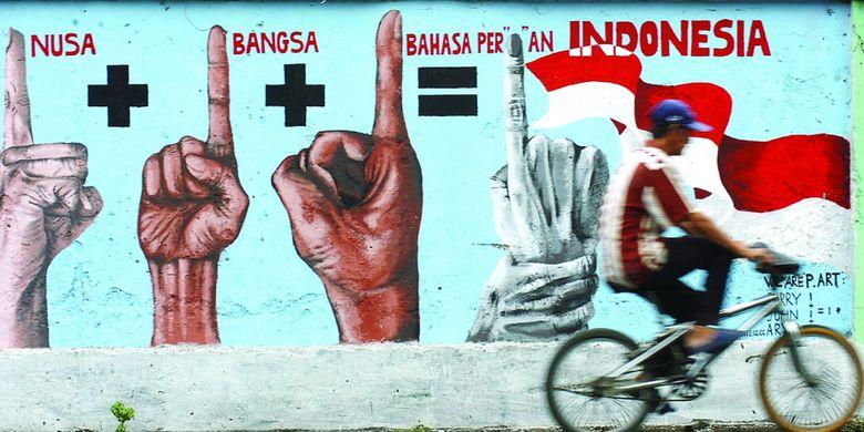 Pengendara sepeda melintasi mural yang mengobarkan semangat persatuan dan kesatuan di Jalan Dinoyo Surabaya, Jawa Timur, Senin (27/10/2008).