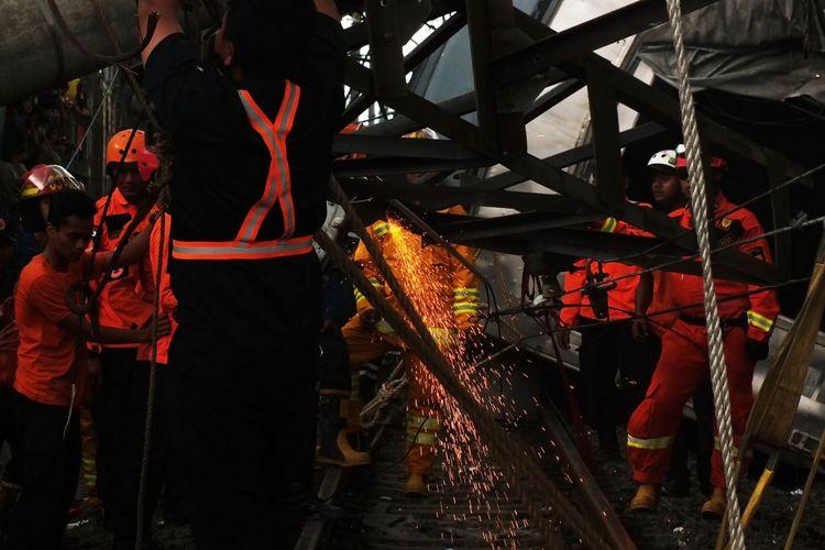 Petugas sedang berusaha memotong tiang listrik yang sempat ditabrak oleh kereta commuter line yang anjlok di perlintasan rel Kebon Pedes, Kota Bogor, Minggu (10/3/2019).