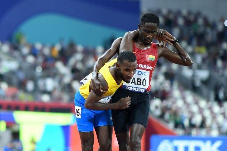 Braima Dabo menuntun Jonathan Busby hingga bisa menyelesaikan balapan lari 5.000 meter putra pada Kejuaraan Dunia Atletik 2019 di Doha, 27 September 2019.
