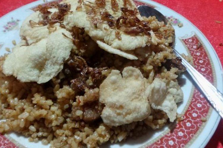 Seporsi nasi goreng dengan taburan bawang goreng dan daging kambing beserta kerupuk emping.