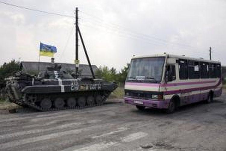 Sebuah bus melintas di dekat tank pasukan Ukraina yang berjaga di pinggiran kota Donetsk yang dianggap kota terbesar si Ukraina timur.