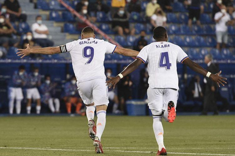 Penyerang Real Madrid asal Perancis, Karim Benzema, melakukan selebrasi bersama David Alaba usai berhasil menjebol gawang Alaves dalam laga Liga Spanyol 2021-2022 di Stadion Mendizorroza, 14 Agustus 2021.