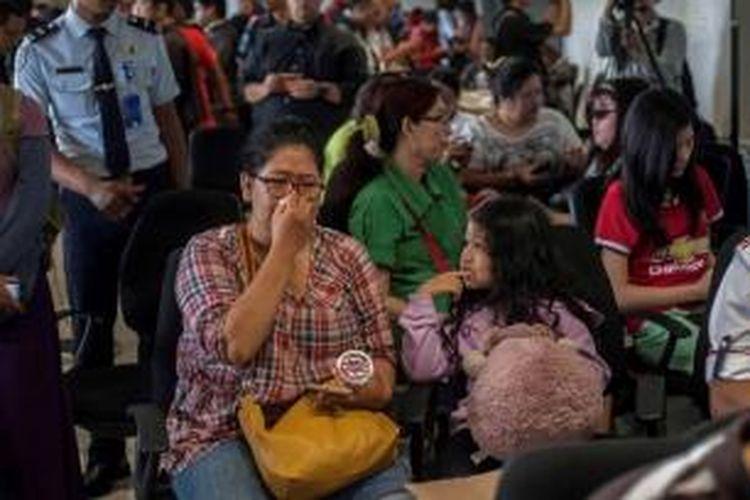 Keluarga penumpang pesawat AirAsia QZ8501 berkumpul di Bandara Juanda Surabaya, 28 Desember 2014. Pesawat AirAsia QZ8501 yang mengangkut 155 penumpang serta 7 awak, hilang kontak pada Minggu pagi, saat penerbangan dari Surabaya menuju Singapura.