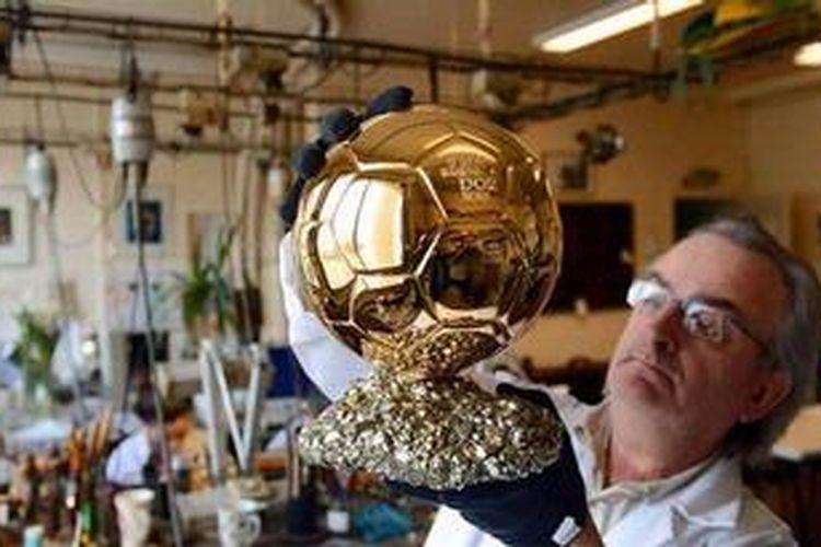 Seniman Perancis, Michel Garault, memeriksa trofi FIFA Ballon dOr yang dibuatnya, di Mellerio Jewelery Workshops, Paris, 6 Desember 2012.