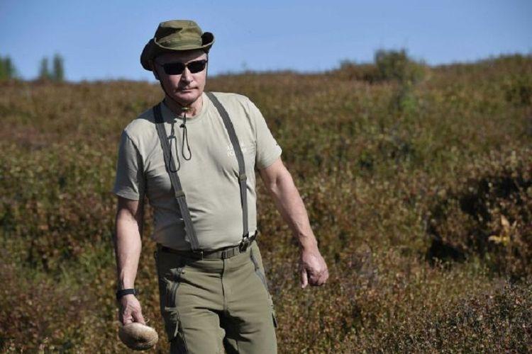 Dalam foto yang dirilis Kremlin, terlihat Presiden Vladimir Putin mengenakan pakaian khaki dan topi ketika menyusuri hutan di Region Tuva, Siberia, pada pekan lalu.