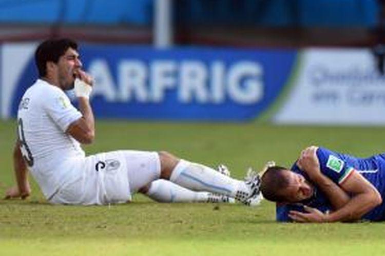 Penyerang Uruguay Luis Suarez (kiri) bereaksi setelah menggigit bek Italia Giorgio Chiellini dalam laga Grup D Piala Dunia di Dunas Arena di Natal, Rabu (25/6/2014). Uruguay menang 1-0.