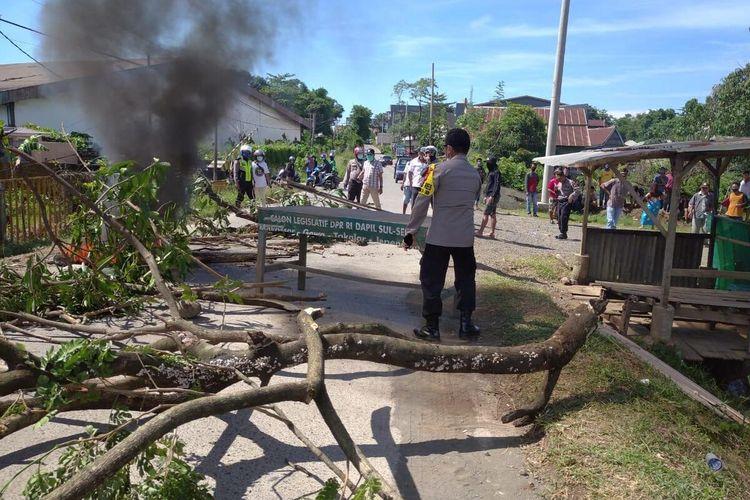 parat kepolisian di Kabupaten Gowa, Sulawesi Selatan tengah melakukan pengamanan saat warga memblokade akses jalan ke pemakaman pasien covid-19. Kamis, (2/4/2020).