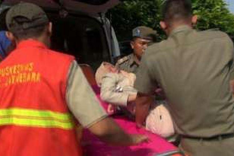 Petugas Puskesmas Kecamatan Jatinegara menggotong seorang Ibu yang pingsan saat antre daging murah bagi pemilik KJP di kantor Kecamatan Jatinegara, Jakarta Timur, Senin (27/6/2016).
