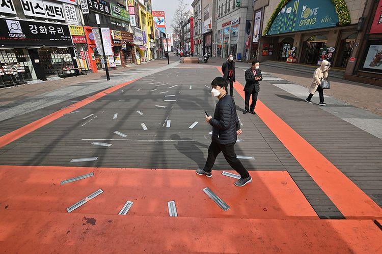 Pejalan kaki yang mengenakan masker di distrik perbelanjaan Dongseongro di kota tenggara Daegu pada 21 Februari 2020