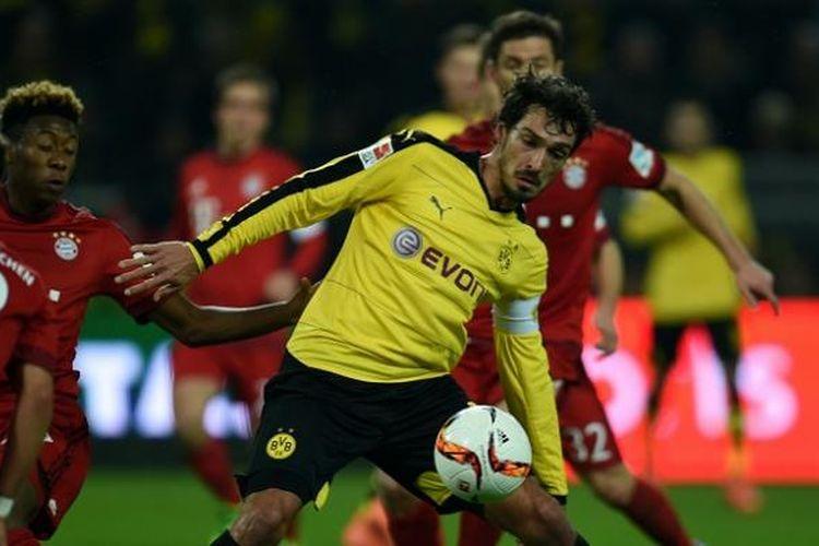 Bek Borussia Dortmund, Matt Hummels, berupaya mempertahankan bola dari para pemain Bayern Muenchen, pada laga Bundesliga di Stadion Signal Iduna Park, Sabtu (5/3/2016) waktu setempat.