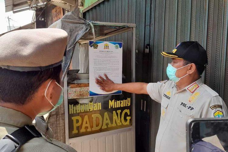 Petugas Satpol PP Kota Serang menempelkan imbauan di salah satu rumah makan, Rabu (14/4/2021).