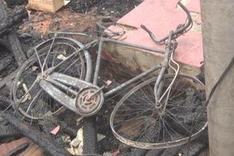 Sebuah sepeda terlihat tergeletal dalam kondisi rusak parah setelah tak bisa diselamatkan dari rumah yang terbakar di Desa Talang Pangeran Ilir, Kecamatan Pemulutan, Kabupaten Ogan Ilir, Sumsel, Selasa (15/9/2015).