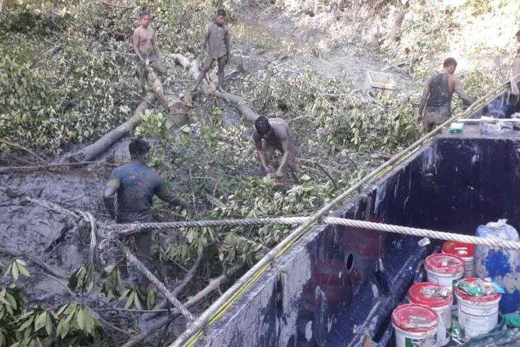 Polisi bergelimang lumpur saat proses evakuasi kapal hantu di hutan bakau Padang Jati OKI, Sumsel, Jumat (11/6/2021).