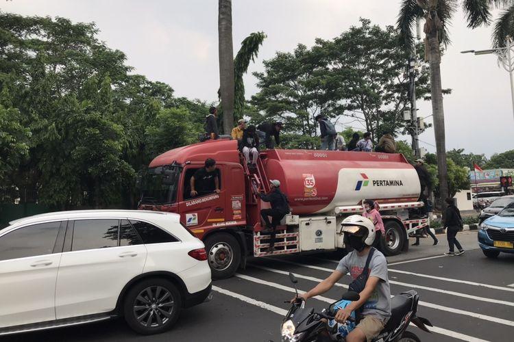 Sejumlah pelajar mencoba naik truk pembawa bahan bakar milik Pertamina yang sedang melintas di Jalan Raya Pondok Indah, Jakarta pada Kamis (8/10/2020) sore.
