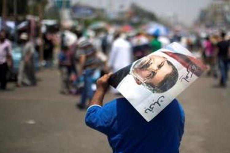 Seorang pendukung presiden terguling Muhammad Mursi memegang poster sang presiden di ibu kota Kairo, Aksi kekerasan di seluruh mesir pasca-tergulingnya Mursi sudang menewaskan 36 orang dan melukai ratusan orang lainnya.