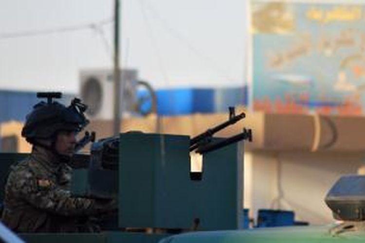 Seorang polisi Irak berjaga di kota Fallujah menyusul serangan kelompok militan ke sebuah kantor polisi kota itu Senin (21/10/2013) yang menewaskan dua polisi dan mencederai empat orang lainnya.