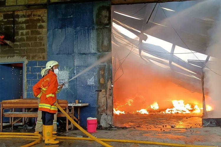 Petugas memadamkan api saat kebakaran melanda Gudang ekspedisi di Jalan Kapuk Kayu Besar, Kelurahan Kamal Muara, Kecamatan Penjaringan, Jakarta Utara pada Rabu (6/10/2021).