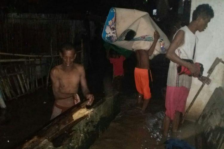 Warga saat menyelamatkan barang-barang dari dalam rumah saat banjir mulai menerjang desa mereka pada Kamis (4/4) malam